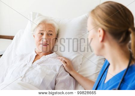 medicine, age, support, health care and people concept - doctor or nurse visiting and cheering senior woman lying in bed at hospital ward