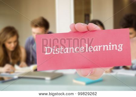 The word distance learning and hand showing card against smiling friends students revising together