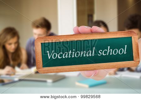 The word vocational school and hand showing chalkboard against smiling friends students revising together