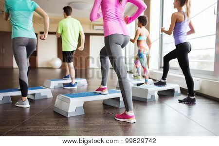 fitness, sport, training, aerobics and people concept - close up of people working out with steppers in gym from back