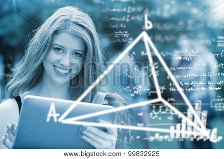 Maths equations against pretty student smiling at camera using tablet pc