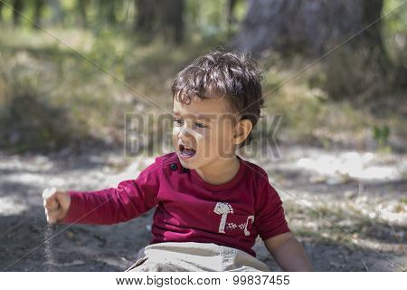 Naughty Boy Sitting On The Sand And Yells