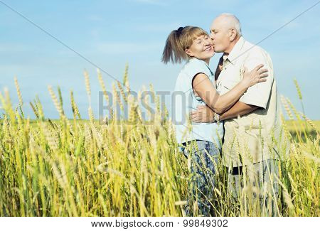happy couple: sixty eight year old man and sixty five year old woman outdoor at the wheat field