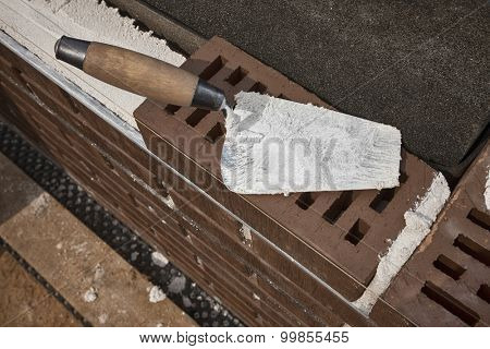 Mason's trowel on brown clinker brick. Masonry concept.