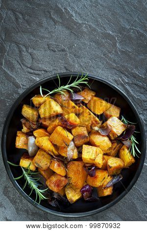 Roasted sweet potato with red onion and rosemary.  Black dish, overhead view, over dark slate.