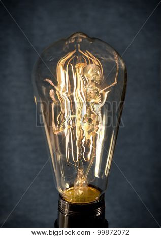 Horrifying vintage Halloween themed skeleton trapped inside lightbulb