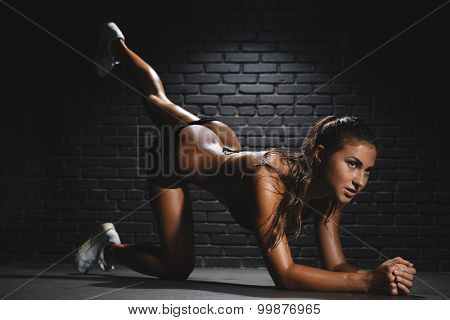Sporty slim woman with ponytail doing exercises for buttocks