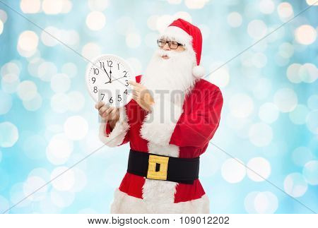 christmas, holidays, time and people concept - man in costume of santa claus with clock showing twelve pointing finger over blue holidays lights background