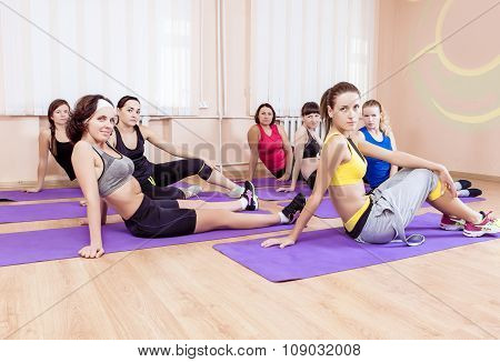 Sport, Training Anf Healthy Lifestyle Concepts. Group Of Seven Caucasian Women Sitting On Floor Mats