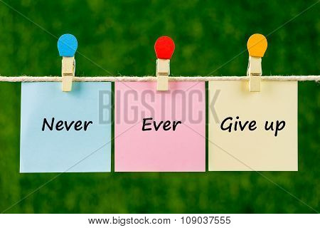 Words Of Never Ever Give Up On Sticky Color Papers Hanging By A Rope.