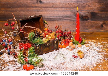 Christmas Winter Still Life With Opened Full Chest, Candle, Apple, Nuts, Cones, Berries, Fir Tree An