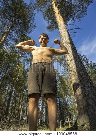 Young Man Stands In A Forest Sports Pose.