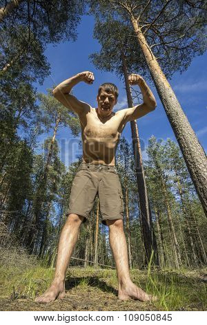 Young Man Stands In The Forest With His Hands Up.