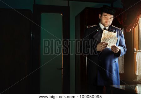 Man In Retro Uniform Stands At The Window, Holding Manuscript.