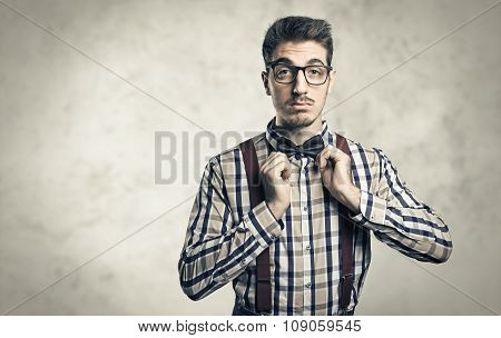 Funny portrait of young nerd with eyeglasses isolated on background.