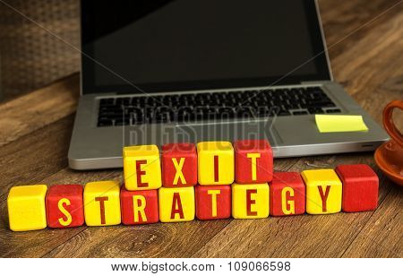 Exit Strategy written on a wooden cube in a office desk poster