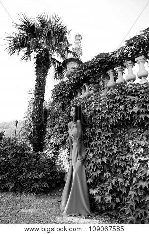 Mulatto Girl Wears Elegant Coral Dress With Bijou ,posing Beside Antic Palace