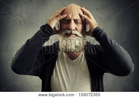 emotional bearded man holding his head and wincing in pain over grey background