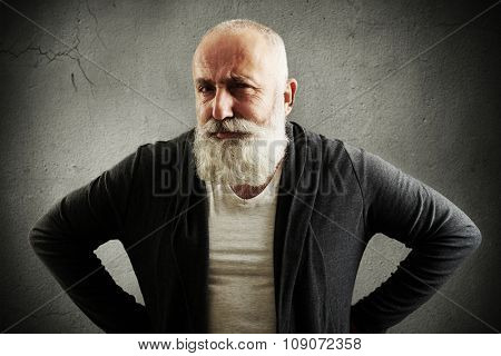 trendy senior man looking at camera with interest over dark grey wall