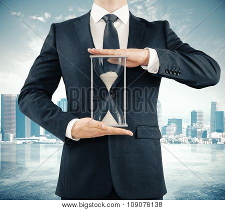 Businessman Holding Hourglass At Megapolis City Background, Time Concept