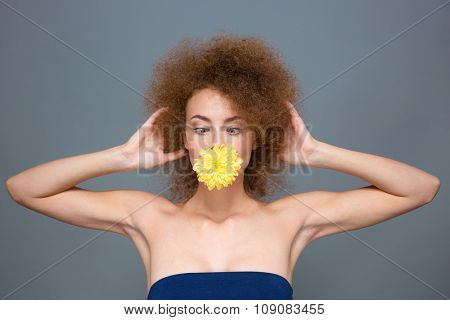 Amusing curly funny pretty girl with yellow flower in mouth kidding and squinting