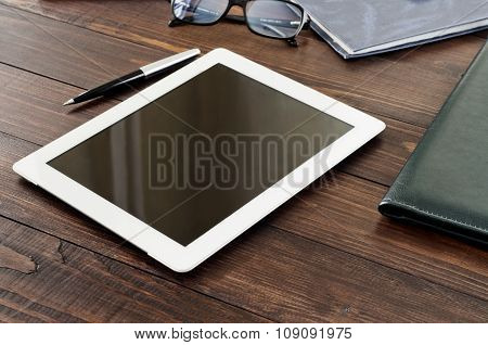 White Tablet Computer On A Wooden Table