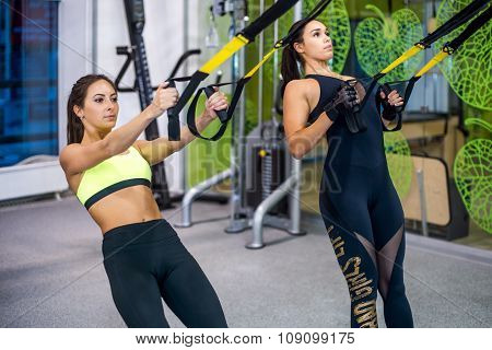 Woman exercising with suspension straps in fitness club or gym.