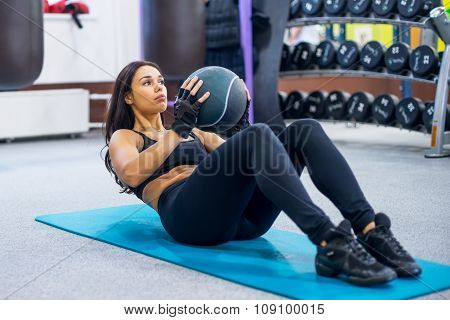 Work out fitness woman doing sit ups abs abdominal crunches core exercises with medecine ball.