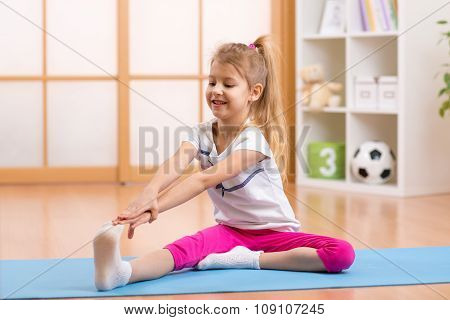 Sportive kid doing gymnastic at home