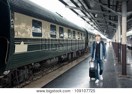 Young Asian Tourist With Luggage Waiting Train In Station.