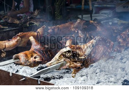 Typical Sardinian Food. Piglets Roast Cooking In The Bbq In A Typical Sardinian Community Festival.