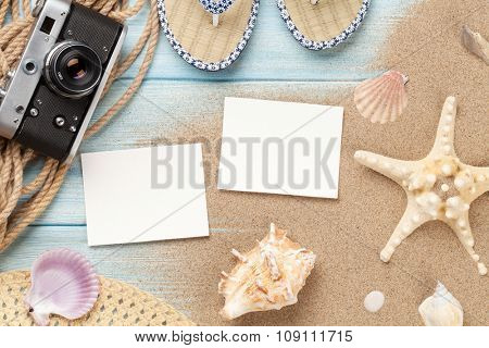 Travel and vacation photo frames and items on wooden table. Top view