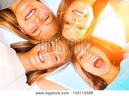 Girlfriends staying together, looking at camera and laughing over blue sky. Group of Four Teenage Girls having fun outdoors. Friendship concept. Group of smiling Joyful girlfriends making a huddle