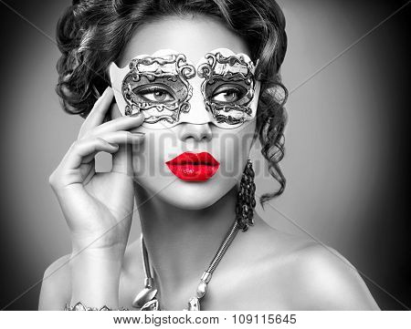 Beauty model woman wearing venetian masquerade carnival mask at party. Christmas and New Year celebration. Sexy girl with holiday makeup.Black and white portrait with Red lips