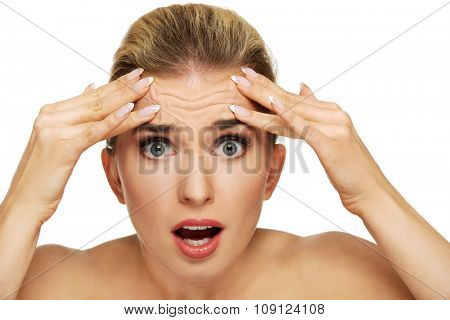 A young woman checking wrinkles on her forehead, closeup poster