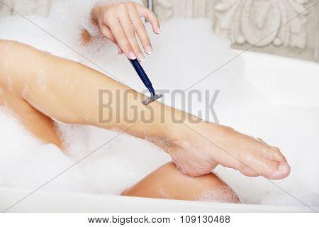Woman shaving her leg with razor in bathroom. poster