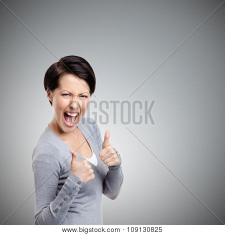 Emotional pretty girl gives thumb up, isolated on grey