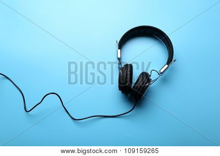 Black headphones on blue background