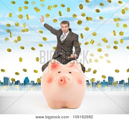 Businessman sitting on piggy bank with money rain
