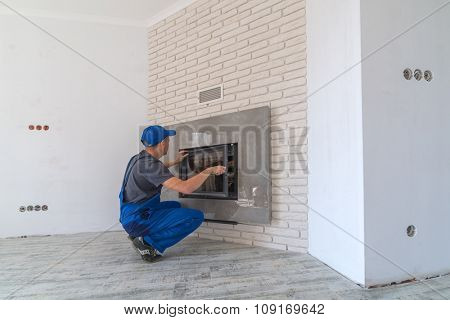 Fireplace installing in white brick wall