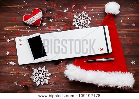 Christmas And New Year Background With Smartphone, Red Santa's Hat, Notepad With Pen And Decorations