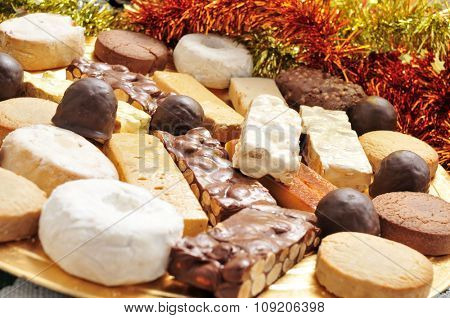 closeup of a golden tray with different turron, mantecados and polvorones, typical christmas confections in Spain poster