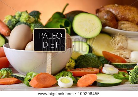 closeup of a signboard with the text paleo diet on a table full of different raw vegetables, a bowl with some chicken eggs and a chicken poster
