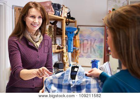 Woman Buying Shirt In Charity Shop