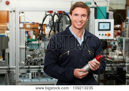 Portrait Of Engineer Holding Component In Factory