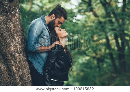 Handsome Man Kissing Beautiful Young Woman In The Forehead