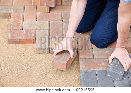 Man Laying Blocks For Patio