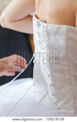 Closeup image of wedding preparations. Bridesmaid is helping put bride elegant luxury dress.