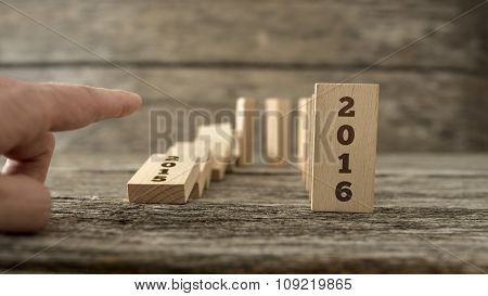 Male Hand Knocking Down A Line Of Domino With The First One Holding A Sign 2015