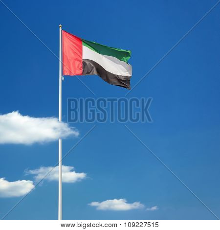 UAE national day: 2nd December. Flag surrounded by clouds.